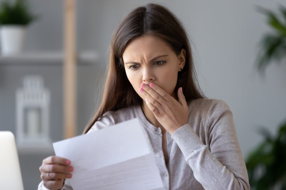 woman looking at car insurance bill