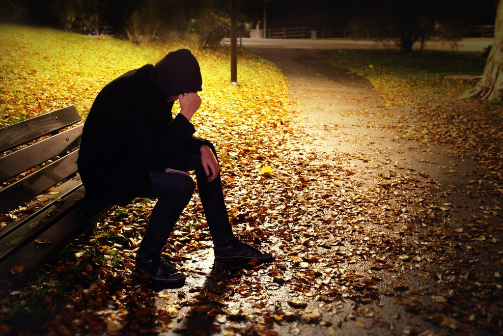 depressed man on a bench with emotional injuries